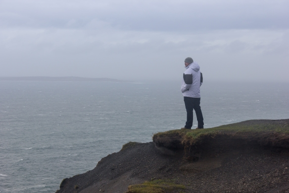 Visitor at Cliffs of Moher looks out at the vista beyond